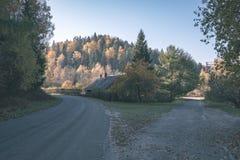 угождать дороге гравия страны чувств или разума астетически в цветах осени в цветах падения с туманом и туманными деревьями на об стоковые фотографии rf