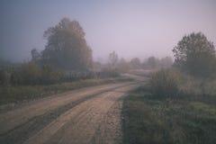 угождать дороге гравия страны чувств или разума астетически в цветах осени в цветах падения с туманом и туманными деревьями на об стоковое фото