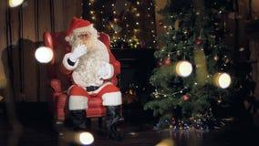 Угождая Санта Клаус сидит в его стул перед рождественской елкой видеоматериал