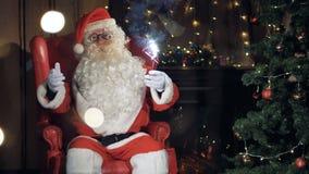 Угождая Санта Клаус сидит в его стул перед рождественской елкой сток-видео
