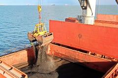 Уголь загрузки от груза barges на судно-сухогруз используя краны и самосхваты корабля на порте Samarinda, Индонезии стоковые изображения