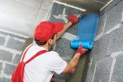 Угол работника штукатура защищая с сеткой технология строительства стоковые изображения rf
