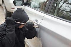 Угонщик пробуя сломать в автомобиль с отверткой Похититель пробуя скомплектовать замок припаркованного автомобиля стоковое фото rf
