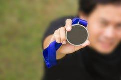 Угол Uprisen азиатского спортсмена держа родовую золотую медаль с r стоковое фото rf