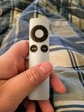 Удаленное ТВ Яблока, который держат в конце-вверх руки стоковые фото