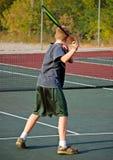 удар справа мальчика играя теннис Стоковая Фотография