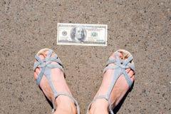 Удачливая женщина находя деньги на улице Ноги женщин рядом с 100 долларовыми банкнотами Потерянные и найденные деньги лежа вниз д стоковые фото