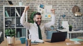 Удачливый молодой человек выражая счастье смотря экран ноутбука в offce акции видеоматериалы