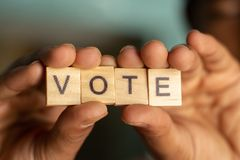 Удержание деревянный показывать писем bloack голосования в руках стоковые изображения