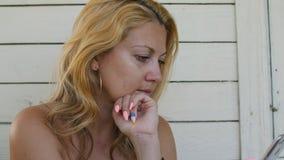 Удерживание взрослой женщины портрета и мобильный телефон использования на деревянной предпосылке стены акции видеоматериалы
