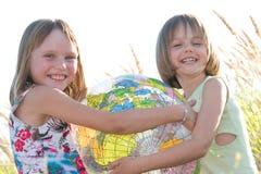 удерживание глобуса девушок счастливое стоковое фото rf