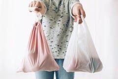 Удерживание женщины в бакалеях одной руки в многоразовой сумке eco и в других овощах в пластиковой сумке полиэтилена Выберите пла стоковое изображение
