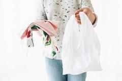 Удерживание женщины в бакалеях одной руки в многоразовой сумке eco и в других овощах в пластиковой сумке полиэтилена Выберите пла стоковые изображения rf