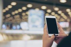 Удерживание женщины и использование белого мобильного телефона с пустым черным экраном пока стоящ и ждущ заявка багажа в авиапорт стоковые фото