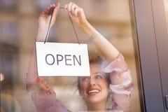 Удерживание женщины открытое подписывает внутри кафе стоковые фотографии rf