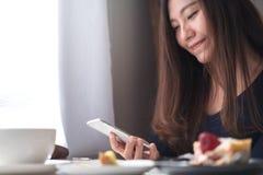 Удерживание женщины smiley красивое азиатское, использование и смотреть умного телефона с белой кофейной чашкой и плитой десерта  Стоковая Фотография RF