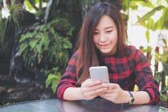 Удерживание женщины smiley красивое азиатское, использование и смотреть умного телефона на внешнем с зеленой предпосылкой природы Стоковое фото RF