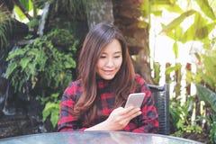 Удерживание женщины smiley красивое азиатское, использование и смотреть умного телефона на внешнем с зеленой предпосылкой природы Стоковая Фотография RF