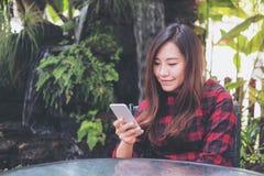 Удерживание женщины smiley красивое азиатское, использование и смотреть умного телефона на внешнем с зеленой предпосылкой природы Стоковая Фотография
