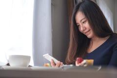 Удерживание женщины smiley красивое азиатское, использование и смотреть умного телефона с белой кофейной чашкой и плитой десерта  Стоковые Изображения