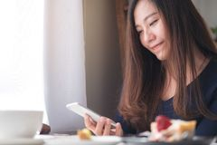 Удерживание женщины smiley красивое азиатское, использование и смотреть умного телефона с белой кофейной чашкой и плитой десерта  Стоковое Фото
