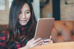 Удерживание женщины smiley красивое азиатское, использующ и смотрящ ПК таблетки сидя в современном кафе Стоковое Изображение RF