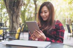 Удерживание женщины smiley красивое азиатское, использующ и смотрящ ПК таблетки с компьтер-книжкой на стеклянном столе сидя на вн Стоковая Фотография RF