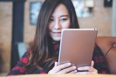 Удерживание женщины smiley красивое азиатское, использующ и смотрящ ПК таблетки сидя в современном кафе Стоковое Изображение