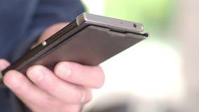 Удерживание и печать бизнесмена в мобильном телефоне Молодая работа бизнесмена с smartphone Взгляд со стороны Отжимать или нажати сток-видео