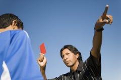 удерживание карточки указывая красный судья-рефери вверх Стоковое Изображение