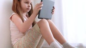 Удерживание маленькой девочки младенца и использование таблетки ПК и сидят на поле в комнате сток-видео