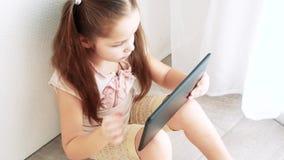 Удерживание маленькой девочки младенца и использование таблетки ПК и сидят на поле в комнате Ребенок уча сделать состав акции видеоматериалы