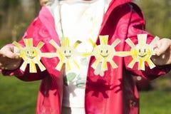 Удерживание маленькой девочки handicrafted бумажные солнца на outdoo солнечного дня стоковое фото rf