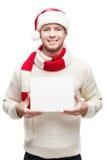 Удерживание молодого человека в знаке шлема santa стоковая фотография rf