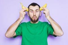Удерживание молодого человека отрезанное в половинном банане на уровне висков стоковое фото rf