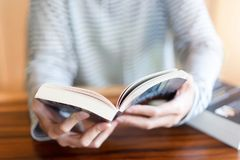 Удерживание руки и прочитать книгу дома стоковое изображение rf