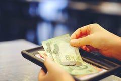 Удерживание руки конца-вверх Билла с тайскими банкнотой и монетками денег Стоковое фото RF