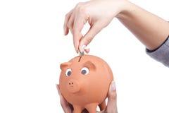 удерживание руки монетки банка piggy Стоковое Изображение RF