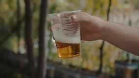 Удерживание руки человека и медленное трясущ чашку прозрачной пластмассы с светлым пивом видеоматериал