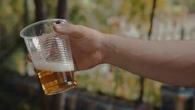 Удерживание руки человека и медленное трясущ чашку прозрачной пластмассы с светлым пивом сток-видео