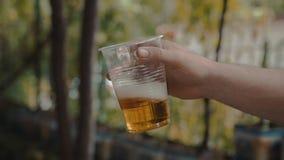 Удерживание руки человека и медленное трясущ чашку прозрачной пластмассы с светлым пивом акции видеоматериалы