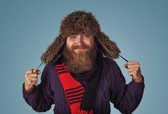 Удерживание человека показывая пушистую меховую шапку в свитере красного шарфа пурпурном стоковое фото rf