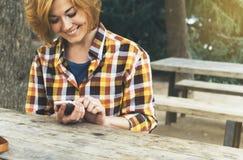 Удерживание человека хипстера в руках цифровом мобильном умном телефоне, чтении улыбки маленькой девочки на устройстве на ландшаф стоковое фото rf