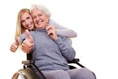 удерживание thumbs вверх по кресло-коляске потребителя стоковые фотографии rf