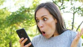 Удивленная взрослая женщина проверяет телефон акции видеоматериалы