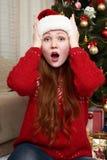 Удивленная голова касания девушки Интерьер дома с украшением, елью и подарками рождества Концепция кануна Нового Годаа и зимнего  Стоковые Фото