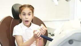 Удивленная девушка рассматривает искусственную челюсть стоковая фотография