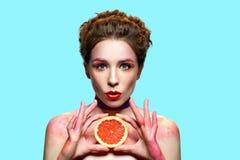 Удивленная женщина держа кусок грейпфрута Стоковое Изображение