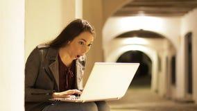 Удивленная женщина находя содержание на ноутбуке в ночи сток-видео