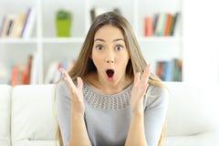 Удивленная женщина смотря камеру дома стоковые фотографии rf